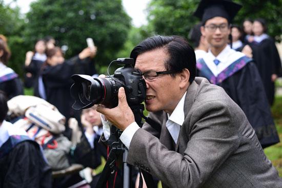 给学生拍毕业照的龚太平。