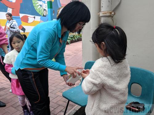 有老师在学校门外为小朋友和家长用酒精洗手液消毒双手。图片来源:香港电台网站/陈青仪 摄